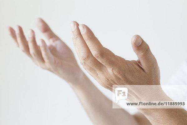 Abgeschnittenes Bild eines Mannes  der die Hände vor weißem Hintergrund gestikuliert.
