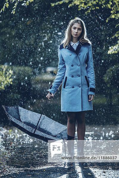 Volle Länge des Teenagermädchens mit Regenschirm auf nassem Fußpfad stehend