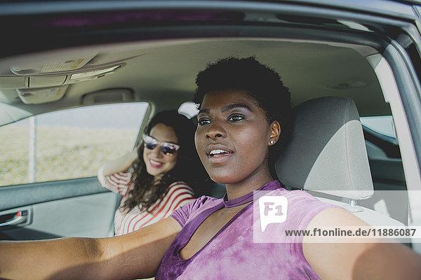 Junge Frau sitzt mit Freundin im Auto und schaut weg  während sie an einem sonnigen Tag im Auto sitzt.