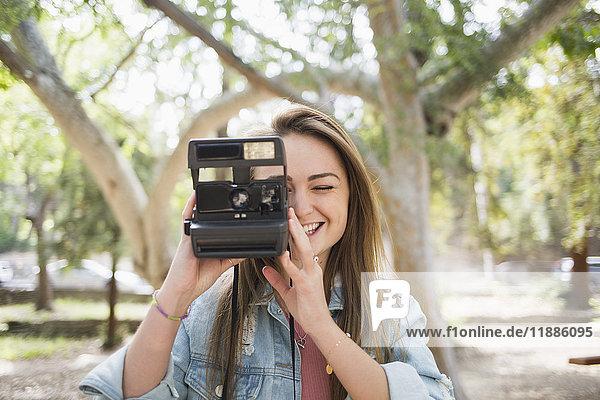 Glückliche junge Frau mit Sofortbildkamera im Park
