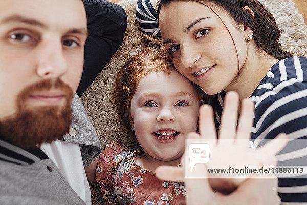 Hochwinkel-Porträt einer lächelnden Familie  die zu Hause auf einem Teppich liegt.