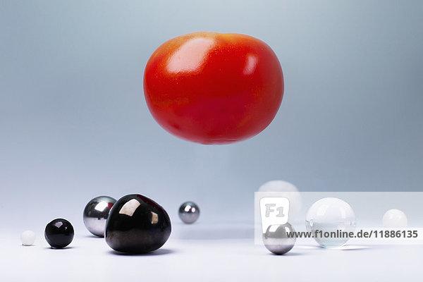 Tomate in der Luft über kleinen runden Objekten unten vor grauem Hintergrund