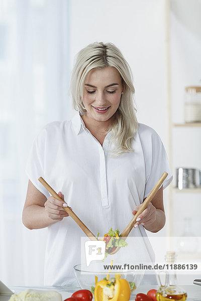 Lächelnde junge Frau wirft frischen Salat auf die Küchentheke zu Hause.