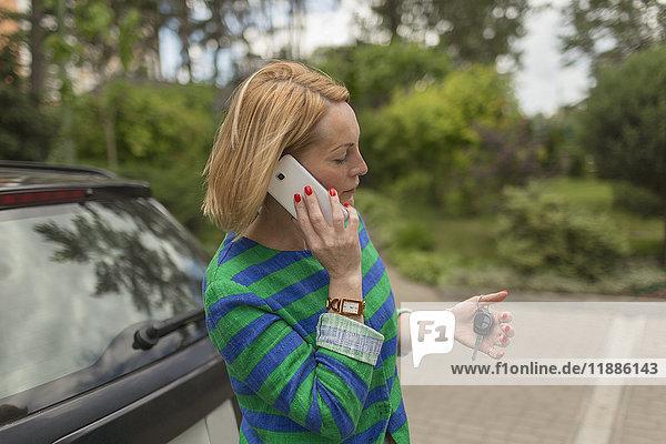 Reife Frau hält den Schlüssel beim Telefonieren mit dem Auto auf der Straße.