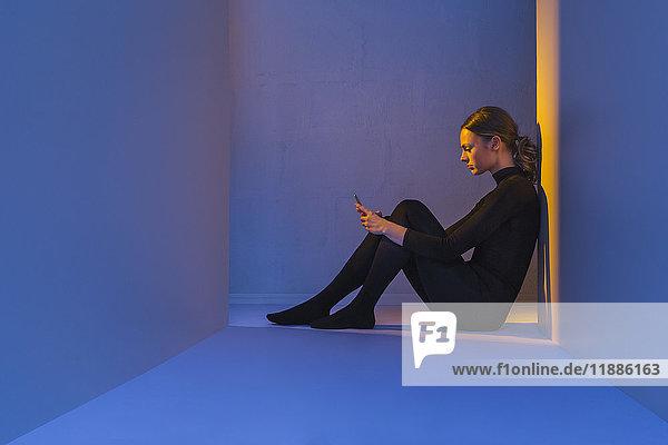 Seitenansicht der jungen Frau beim Sitzen an der Wand im violetten Zimmer