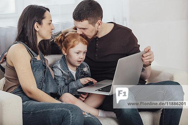Frau sieht den Mann an  der die Tochter küsst  während sie den Laptop im Wohnzimmer hält.