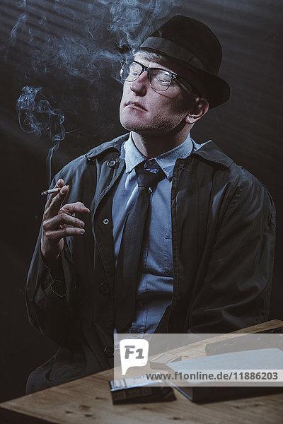 Junger Mann sitzt mit einer Waffe am Tisch und raucht eine Zigarette.
