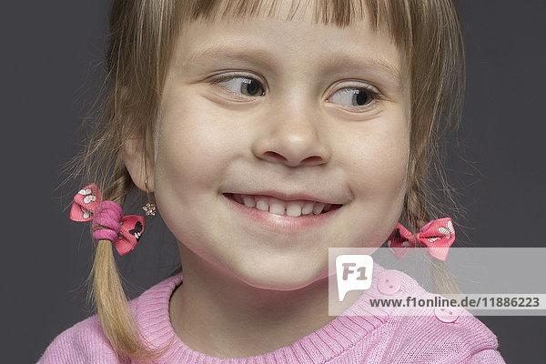 Nahaufnahme des süßen  lächelnden Mädchens mit rosa Pullover auf grauem Hintergrund