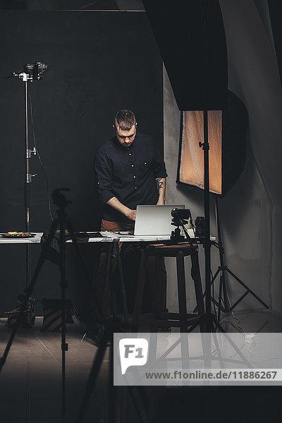 Fotograf  der am Laptop arbeitet  während er vor der Kulisse des Studios steht.