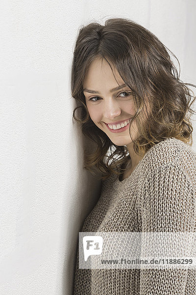 Lächelnde schöne Frau an der weißen Wand stehend