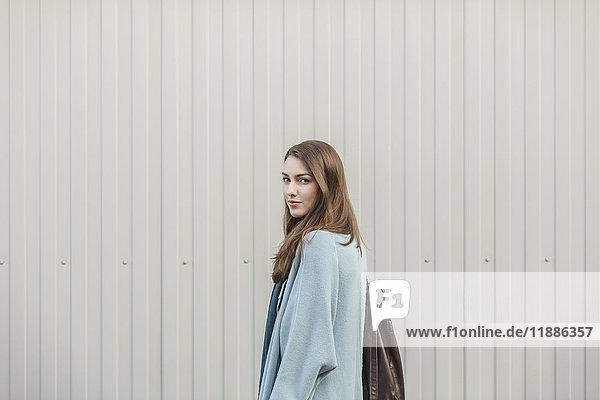 Porträt einer schönen jungen Frau  die einen Rucksack trägt  während sie an der Wand steht