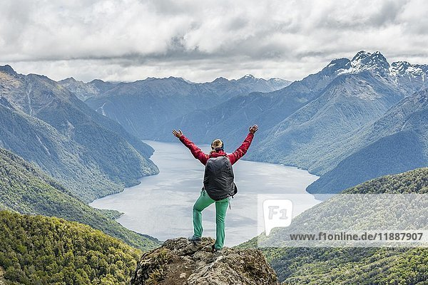 Female hiker is looking at the South Fiord of Lake Te Anau  stretching arms in the air  at back the Southern Alps  the Kepler Track hiking trail  Fiordland National Park  Southland  New Zealand  Oceania