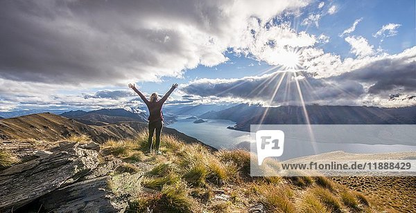 Hiker stretching arms in the air  sun shining  Lake Wanaka and mountain landscape  Isthmus Peak  Otago  South Island  New Zealand  Oceania