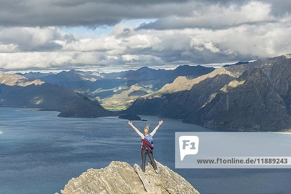 Female hiker on a rock  stretching arms in the air  Lake Hawea and mountain landscape  Isthmus Peak  Otago  South Island  New Zealand  Oceania