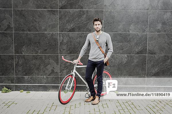 Porträt eines jungen Mannes mit seinem Rennrad