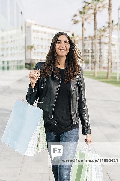 Porträt einer lächelnden Frau mit Einkaufstaschen