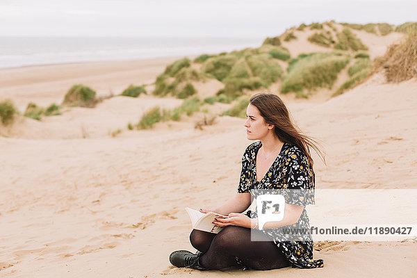 Nachdenkliche junge Frau am Strand sitzend mit einem Buch