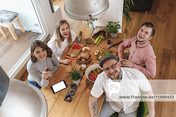 Portrait of four friends preparing food together at home