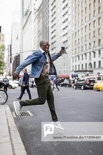 USA  New York City  Manhattan  stilvoller Mann beim Sprung in die Luft
