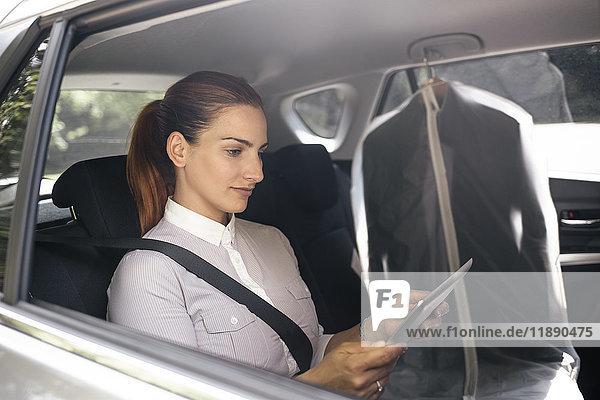 Geschäftsfrau auf dem Rücksitz eines Autos sitzend mit Tablette