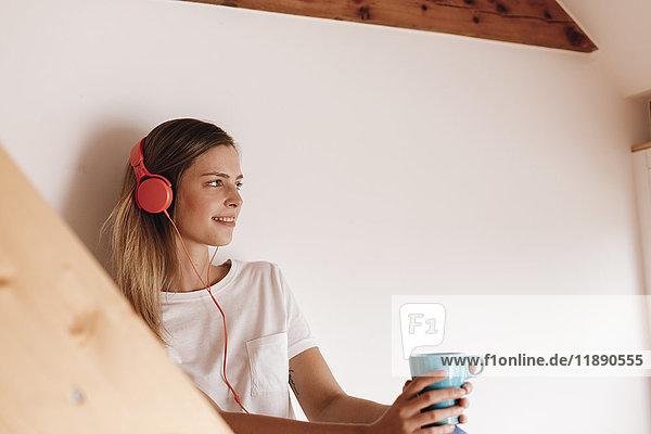 Junge Frau entspannt zu Hause bei einer Tasse Tee  Musik hören