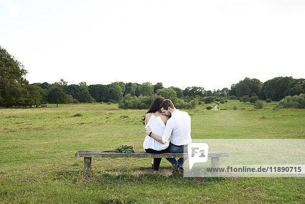 Rückansicht eines Paares auf einer Bank im Park
