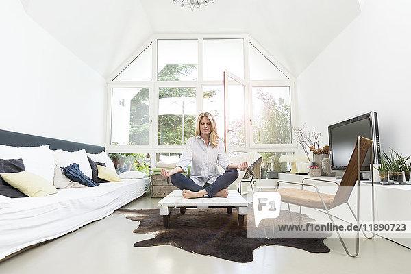 Blonde Frau auf dem Couchtisch sitzend  meditierend