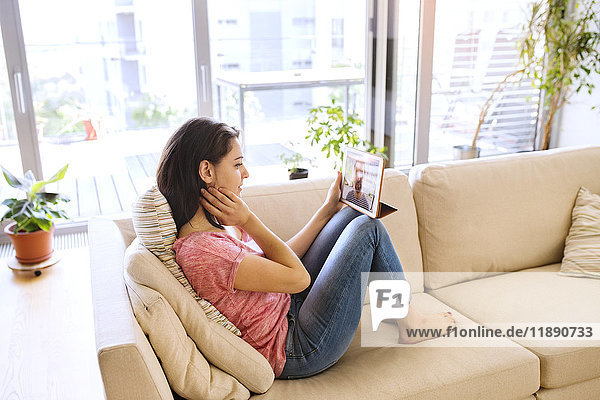 Junge Frau nutzt Tablett für Videochat zu Hause
