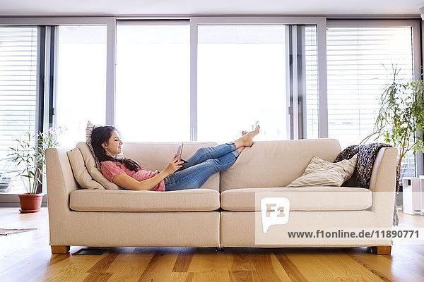 Junge Frau auf der Couch liegend mit Tablett für Videochat zu Hause