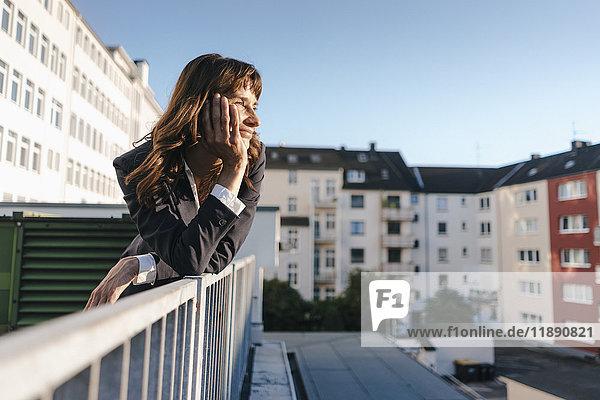 Geschäftsfrau  die auf dem Balkon steht und die Sonne genießt. Geschäftsfrau, die auf dem Balkon steht und die Sonne genießt.