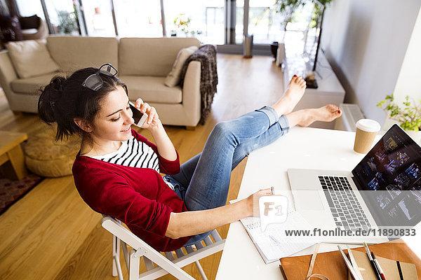 Lächelnde Frau am Telefon  die zu Hause am Schreibtisch arbeitet.