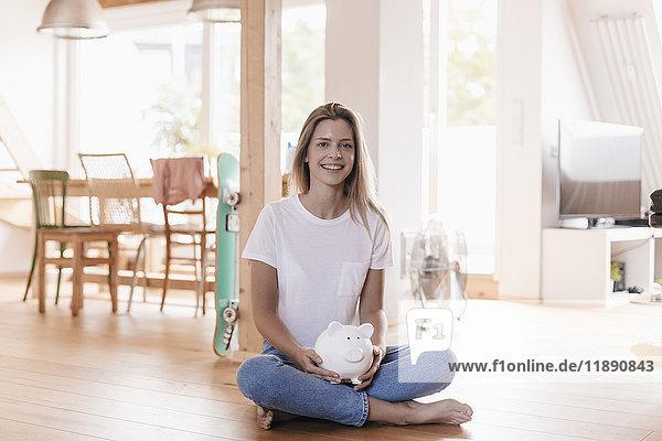 Frau sitzt auf dem Boden und hält Sparschwein.