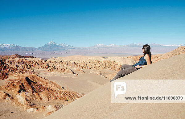 Chile  Atacama-Wüste  Frau auf der Düne sitzend mit Blick auf die Aussicht