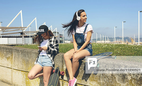 Young woman with headphones listening music while her friend looking at smartphone