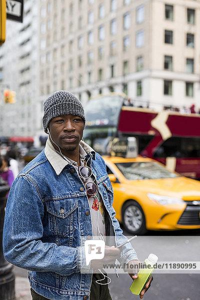 USA  New York City  Manhattan  portrait of stylish man with earphones and smartphone