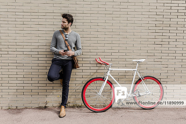 Porträt eines jungen Mannes mit Rennrad und Handy an der Wand lehnend