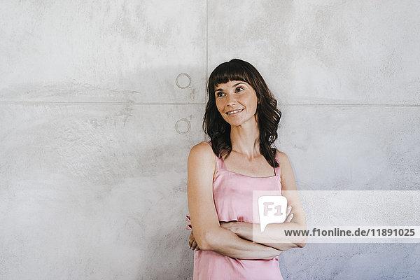 Geschäftsfrau lehnt sich mit gekreuzten Armen an die Wand