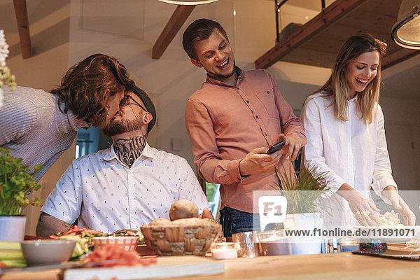 Freunde  die zu Hause gemeinsam Essen zubereiten