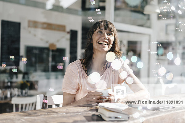 Woman sitting cafe  watching soap bubbles