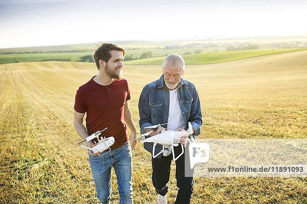 Senior Vater und sein erwachsener Sohn mit Drohne auf einem Feld