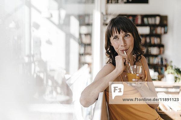 Frau sitzt im Café und trinkt aus einem Glas mit einem Strohhalm.