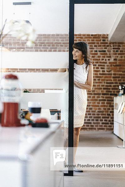 Geschäftsfrau im Büro stehend  um die Ecke schauend