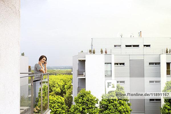 Frau am Telefon auf dem Balkon stehend