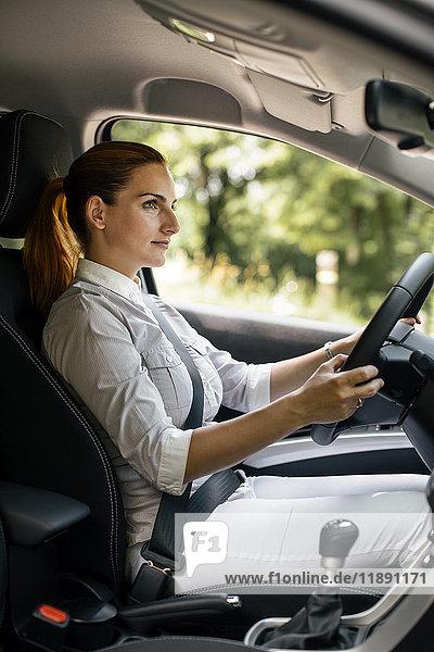 Geschäftsfrau beim Autofahren