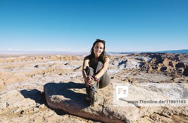 Chile  Atacama-Wüste  lächelnde Frau auf einem Felsen im Sonnenlicht sitzend