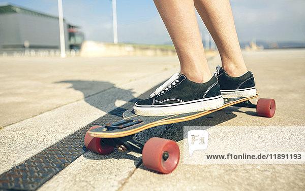 Füße der jungen Frau auf Longboard  Nahaufnahme