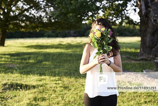 Junge Frau versteckt sich hinter einem Blumenstrauß.