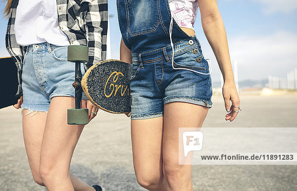 Two young women with longboards in front of beach promenade  partial view