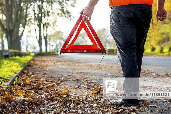 Männerbeine mit Warndreieck am Straßenrand