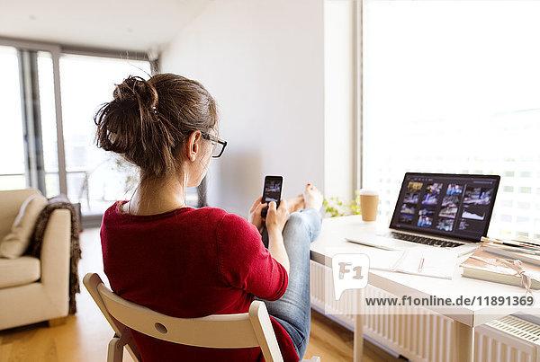 Frau sitzt zu Hause am Schreibtisch mit dem Smartphone